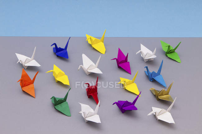 Close-up view of colorful origami cranes on grey background — Stock Photo