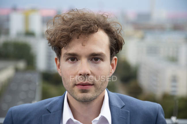 Portrait of businessman with stubble and curly brown hair on roof terrace in the evening — Stock Photo