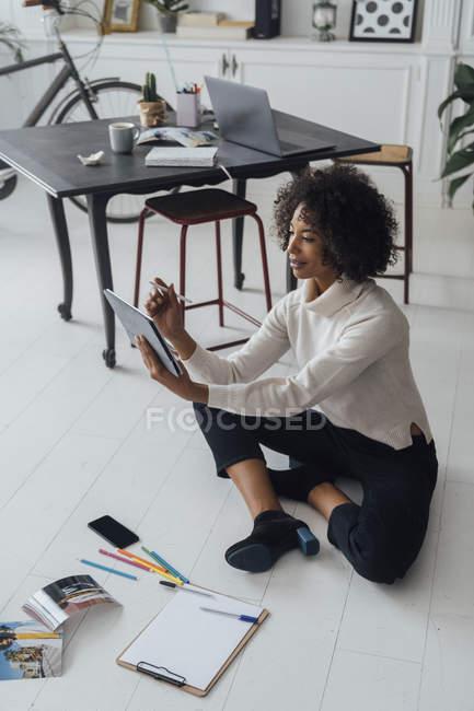Disigner sitzt auf dem Boden ihres Heimbüros und benutzt ein digitales Tablet — Stockfoto