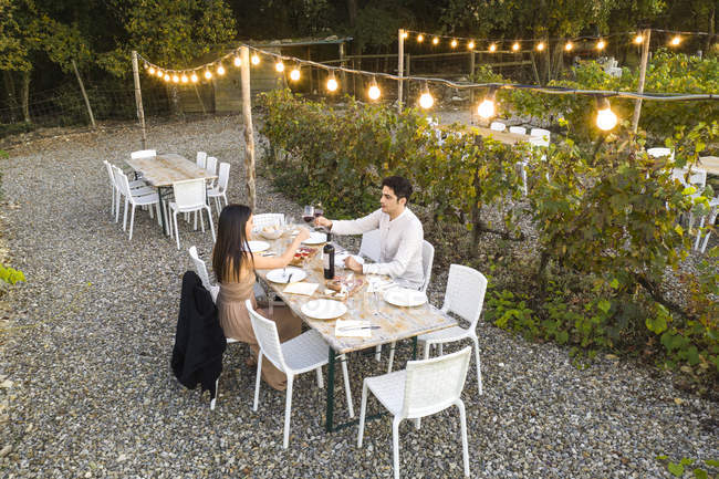 Italy, Tuscany, Siena, young couple having dinner in a vineyard — Foto stock