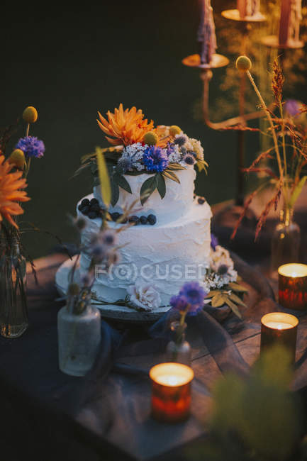 Wedding cake on table with candles outdoors — Stock Photo