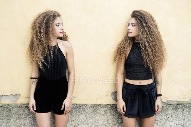 Сестры-близнецы стоят перед стеной и смотрят друг на друга — стоковое фото