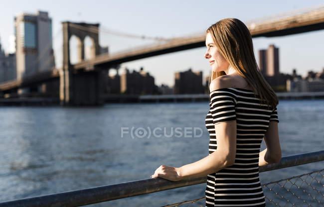 USA, New York, Brooklyn, donna vestita a righe e in piedi davanti all'East River al tramonto — Foto stock