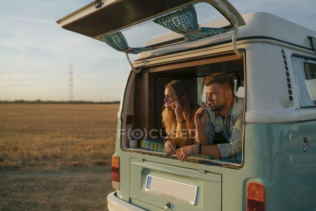 Couple brushing teeth in camper van in rural landscape — Stock Photo