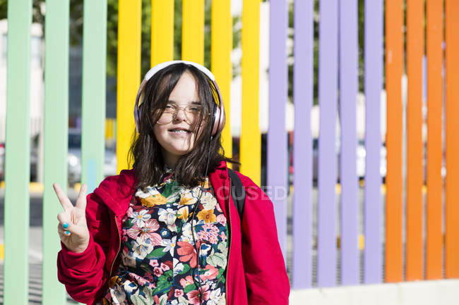 Teenager with down syndrome using smartphone, headphones, peace sign — Stock Photo
