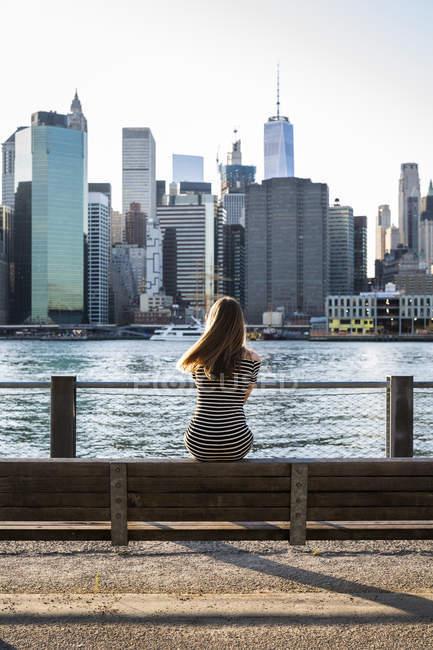 USA, New York, Brooklyn, vista posteriore di una donna seduta sulla panchina di fronte all'East River e allo skyline di Manhattan — Foto stock