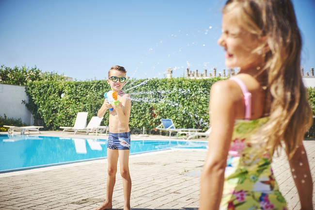 Boy with water gun splashing at girl at the poolside — Stock Photo