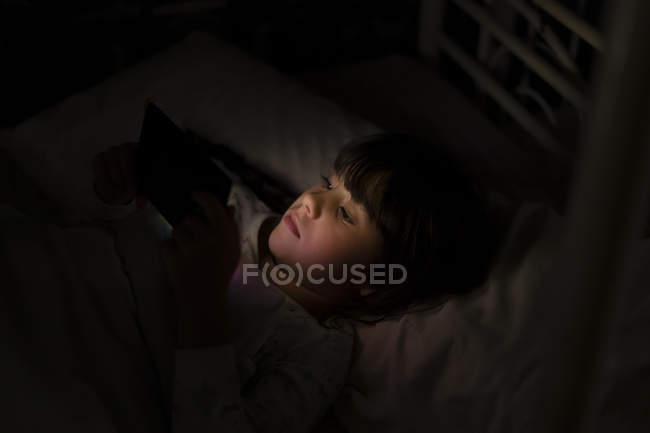Девушка лежит в постели и использует смартфон ночью — стоковое фото