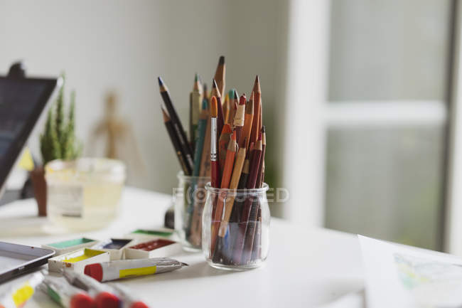 Glasses of coloured pencils, paint tubes and watercolour paints on illustrator's work desk in an atelier — Stock Photo