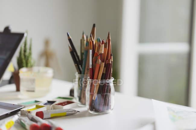 Очки цветных карандашей, трубок и акварельных красок на рабочем столе иллюстратора в ателье — стоковое фото