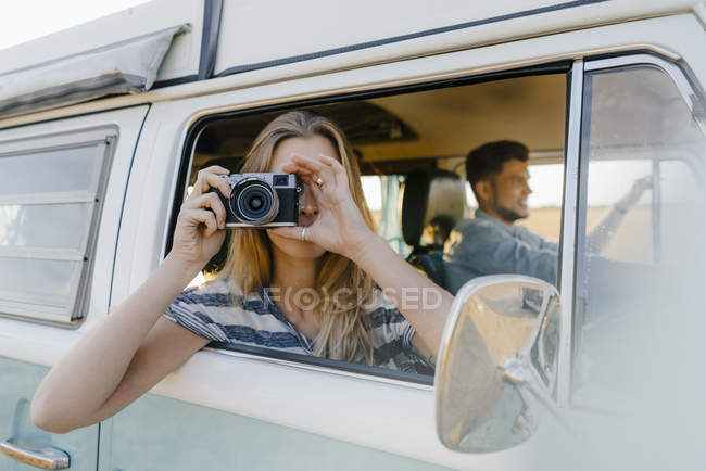 Woman taking picture out of window of a camper van with man driving — Stock Photo