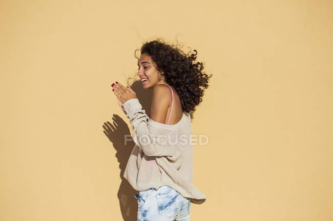 Портрет девочки-подростка в пуловере у оранжевой стены — стоковое фото