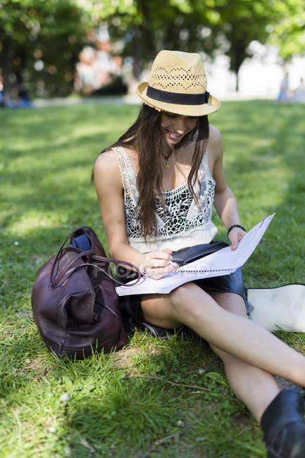 Smiling young student sitting on a meadow in a park and using copybook — Stock Photo