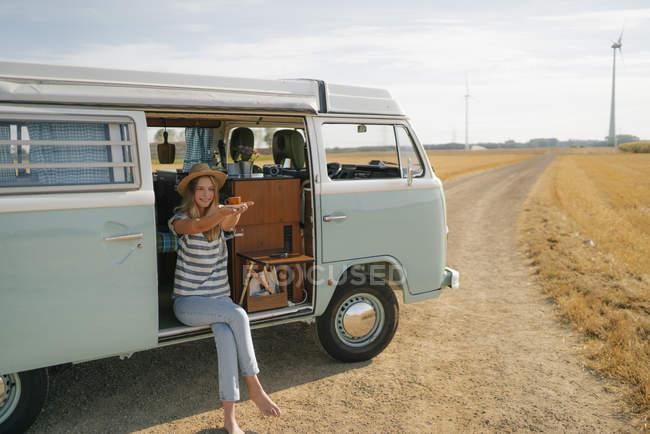 Усміхнена молода жінка тримає чашку кави в кемпер Ван в сільській місцевості — стокове фото