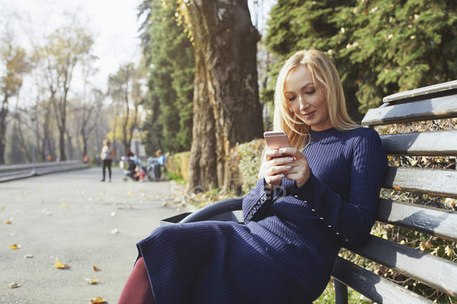 Portrait of blond woman sitting on bench in autumnal city park, using smartphone — Stockfoto