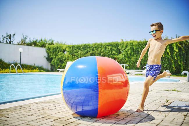 Мальчик в солнцезащитных очках у бассейна пинает большой пляжный мяч — стоковое фото