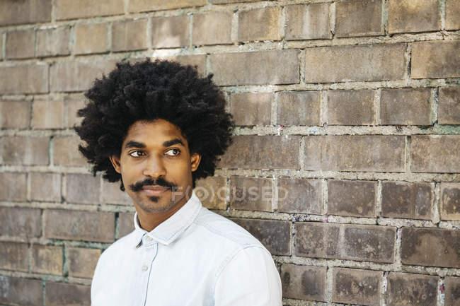 Afrikanisch-amerikanischer Mann steht vor Backsteinmauer, Porträt — Stockfoto