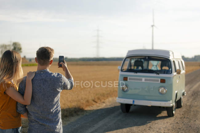 Young couple taking cell phone picture of camper van in rural landscape — Stock Photo