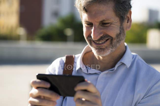 Улыбающийся взрослый мужчина смотрит на мобильный телефон на улице — стоковое фото
