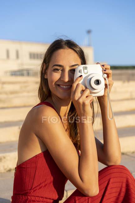 Портрет улыбающейся молодой женщины, делающей мгновенное фото на открытом воздухе — стоковое фото