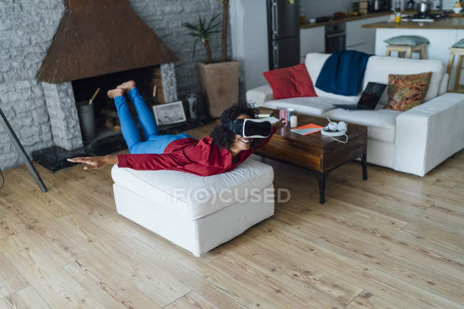 Woman lying on seating furniture, wearing VR goggles, pretending to fly — Stock Photo