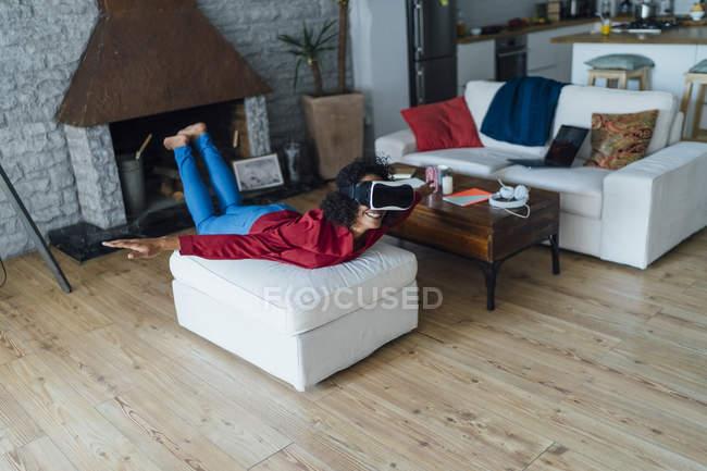 Жінка, що лежить на сидіння меблі, носіння VR окуляри, прикидаючись літати — стокове фото