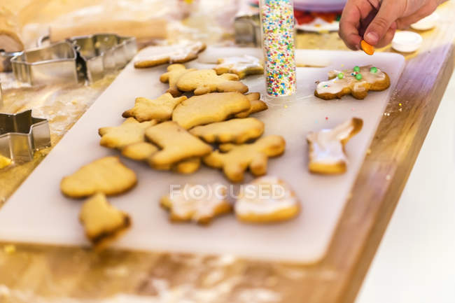 Girl's hand decorating Christmas cookies — Stock Photo