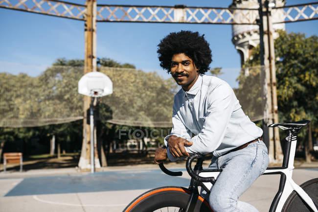 Sorrindo homem sentado em sua bicicleta em um chão de basquete — Fotografia de Stock