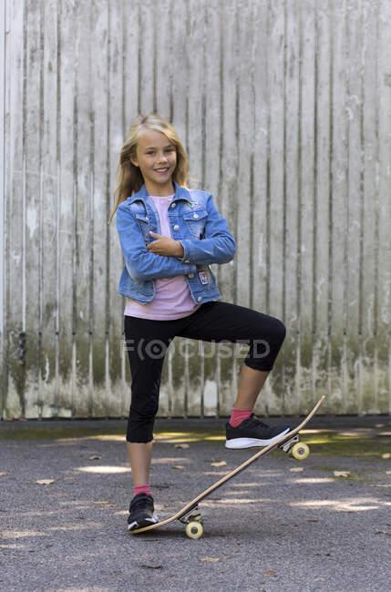 Портрет улыбающейся девушки с скейтбордом — стоковое фото