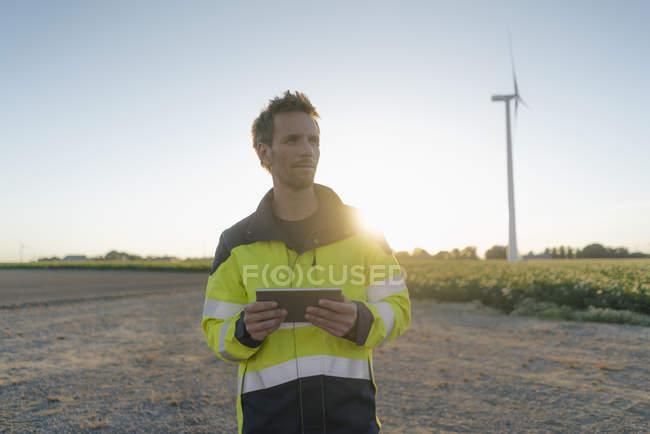 Ingenieur steht in ländlicher Landschaft an einer Windkraftanlage und hält Tablet — Stockfoto