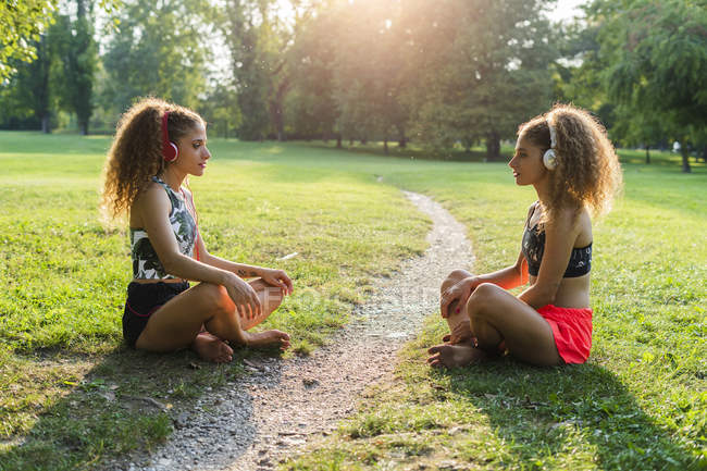 Twin sisters sitting on a medow in a park listening music with headphones — Stock Photo