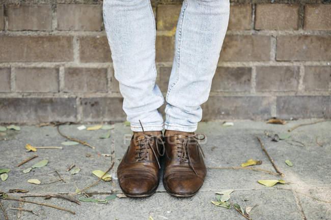 Imagem cortada do homem em pé na frente da parede de tijolo — Fotografia de Stock