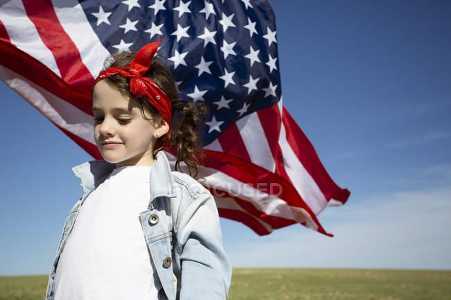 Ragazza con bandiera americana sul campo in un paesaggio remoto — Foto stock