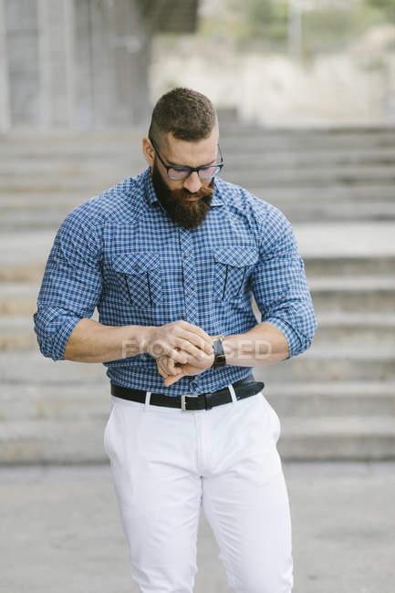 Бородатый хипстер-бизнесмен, проверяющий время — стоковое фото