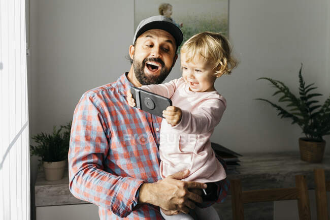 Father holding his little daughter on his arm, playing with his smartphone — Stock Photo