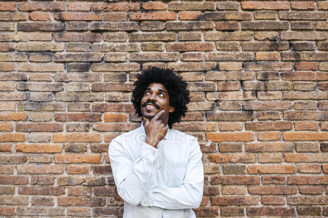African american man standing in front of brick wall, looking up, smiling — Stock Photo
