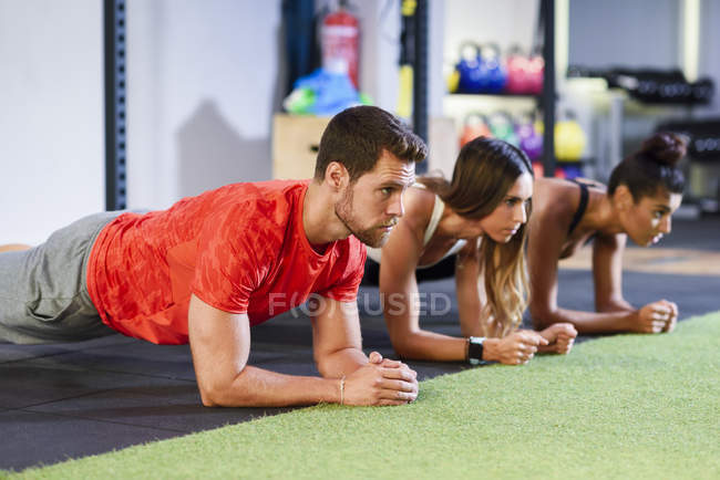 Young people exercising plank variations in a gym — Stock Photo
