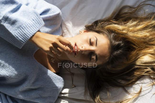 Retrato da mulher nova bonita que encontra-se na cama com olhos fechados — Fotografia de Stock