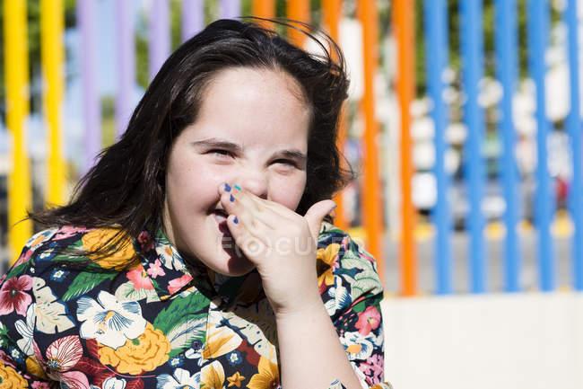 Adolescente menina com síndrome para baixo rindo, mão cobrindo boca — Fotografia de Stock