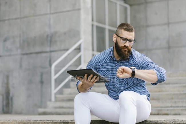 Retrato de hombre de negocios hipster barbudo sentado en las escaleras con tableta digital y comprobando la hora - foto de stock