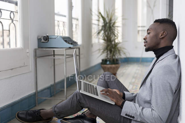 Joven hombre de negocios sentado en el suelo en la oficina, trabajando en el ordenador portátil - foto de stock