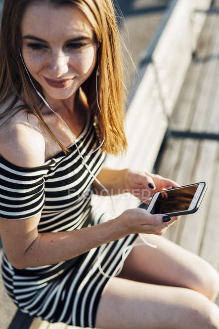 Smiling woman wearing striped dress and listening music with smartphone and earphones — Stock Photo