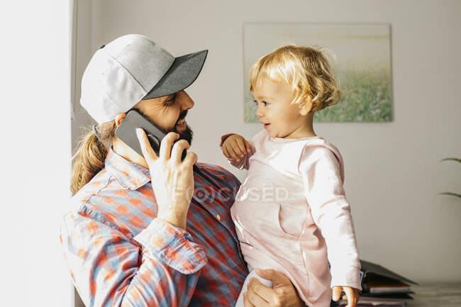 Vater hält seine kleine Tochter auf dem Arm, während er mit seinem Smartphone spricht — Stockfoto