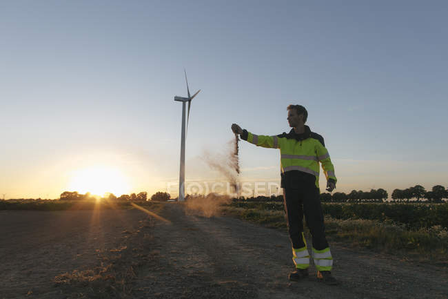 Engineer at a wind turbine at sunset scattering soil — Stock Photo