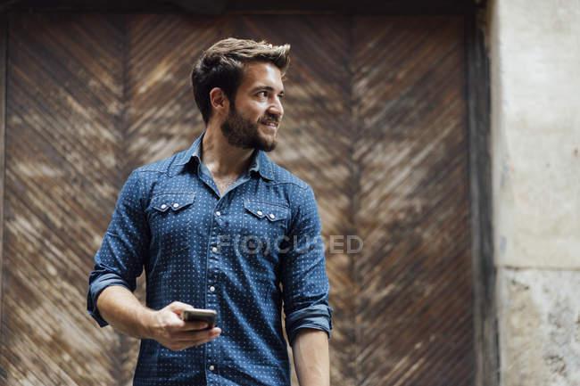 Hombre barbudo con teléfono inteligente mirando a la distancia - foto de stock
