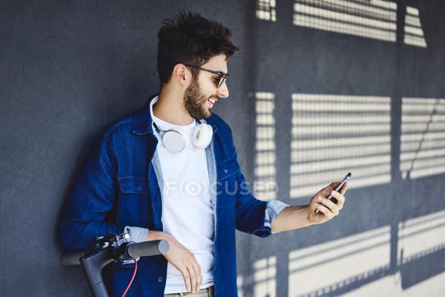 Homme souriant jeune avec scooter électrique regardant le téléphone portable à l'extérieur — Photo de stock