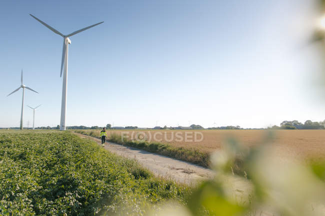 Engineer walking on field path at a wind farm — Stock Photo