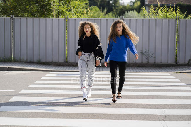 Twins walking on zebra crossing — Stock Photo