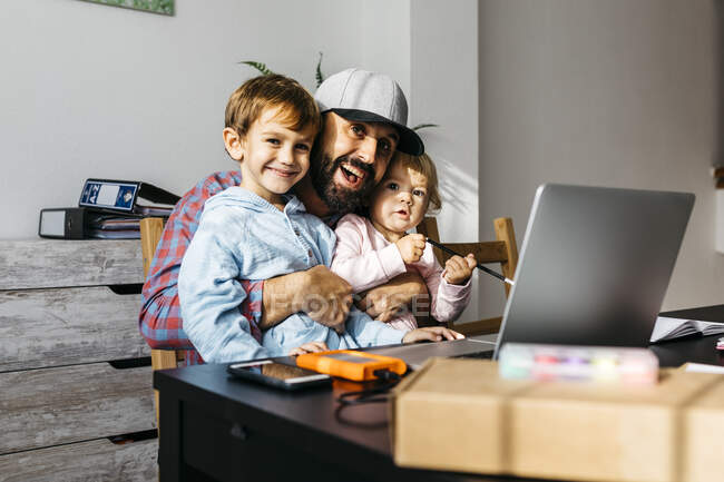 Padre che lavora a casa, usando laptop con i suoi figli sul suo grembo — Foto stock