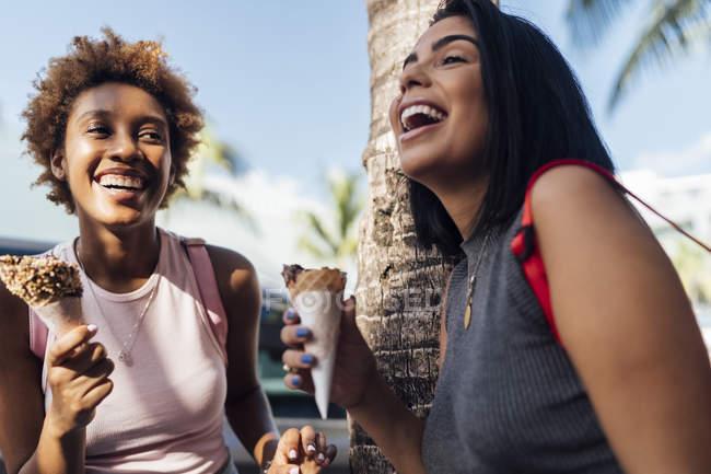 Дві щасливі друзі жінки з конуси морозива в пальмове дерево — стокове фото